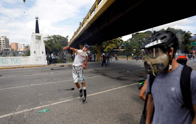 A demonstrator hurls stones during clashes with security forces at a rally against Venezuelan President Nicolas Maduro's government in Caracas, Venezuela, July 6, 2017. REUTERS/Andres Martinez Casares