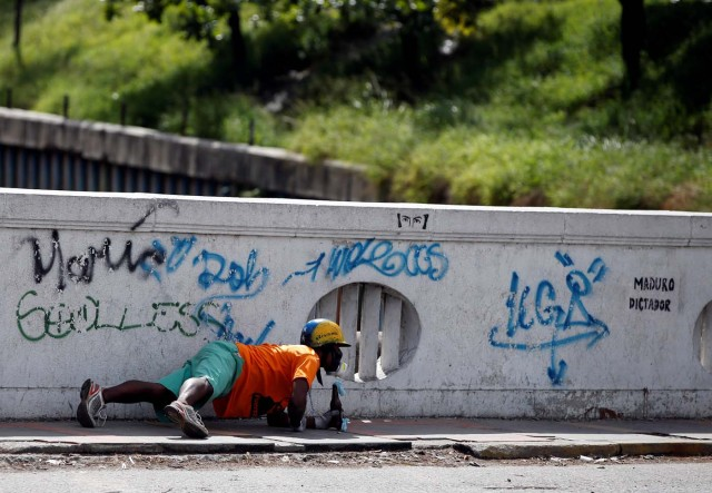 A demonstrator takes cover during clashes with security forces at a rally against Venezuelan President Nicolas Maduro's government in Caracas, Venezuela, July 6, 2017. REUTERS/Andres Martinez Casares