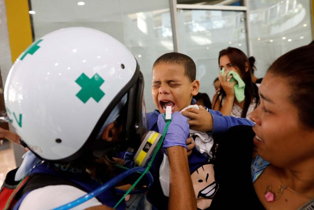 A child receives medical attention outside a shopping mall after being affected by smoke from tear gas fired by security forces during clashes at a rally against Venezuelan President Nicolas Maduro's government in Caracas, Venezuela, July 6, 2017. REUTERS/Andres Martinez Casares