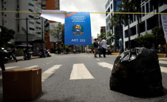 A sign depicting Venezuela's Constitution hangs on a rope at a barricade during a protest against Venezuelan President Nicolas Maduro's government in Caracas, Venezuela July 10, 2017. REUTERS/Carlos Garcia Rawlins