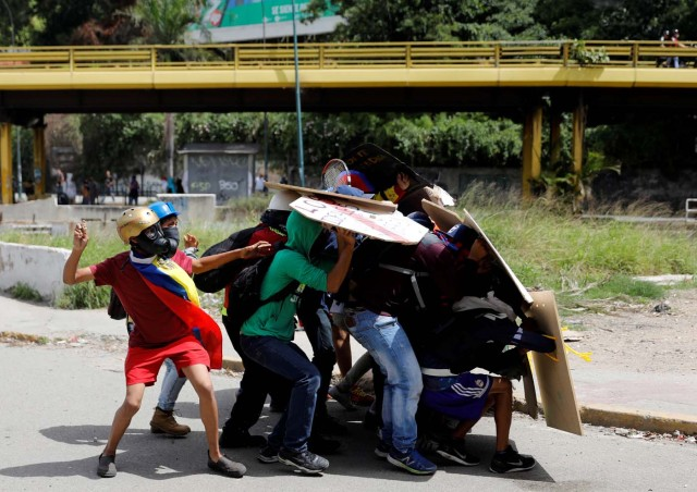 Demonstrators use shields for cover as they throw stones during a protest against Venezuela's President Nicolas Maduro's government in Caracas, Venezuela July 10, 2017. REUTERS/Andres Martinez Casares     TPX IMAGES OF THE DAY