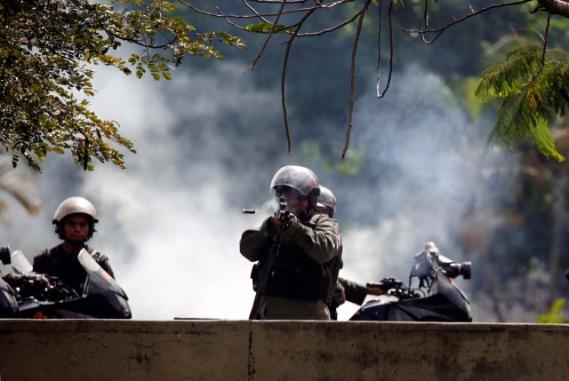 A member of the security forces fires his weapon during a protest against Venezuelan President Nicolas Maduro's government in Caracas, Venezuela July 10, 2017. REUTERS/Carlos Garcia Rawlins
