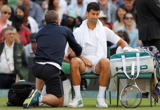 El serbio Novak Djokovic recibe atención médica durante el partido por los cuartos de final de Wimbledon contra el checo Tomas Berdych, en Londres. 12 de julio 2017. REUTERS/Matthew Childs - RTX3B6H7