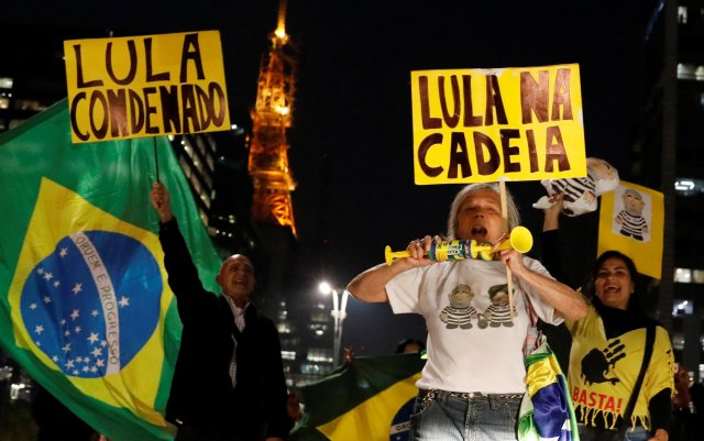 "People celebrate after former Brazilian President Luiz Inacio Lula da Silva, was convicted on corruption charges and sentenced to nearly 10 years in prison in Sao Paulo, Brazil July 12, 2017. The signs read:""Lula was convicted"" and ""Lula in Jail."" REUTERS/Nacho Doce"