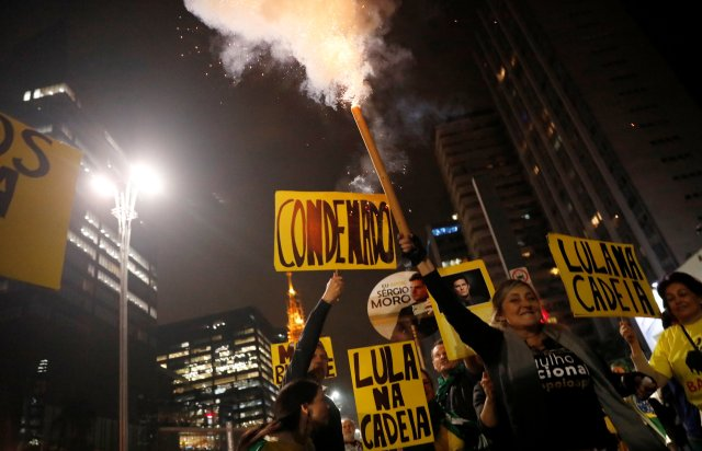 "People celebrate after former Brazilian President Luiz Inacio Lula da Silva was convicted on corruption charges and sentenced to nearly 10 years in prison, in Sao Paulo, Brazil July 12, 2017. The signs read, ""Lula was convicted"" and ""Lula in Jail."" REUTERS/Nacho Doce"