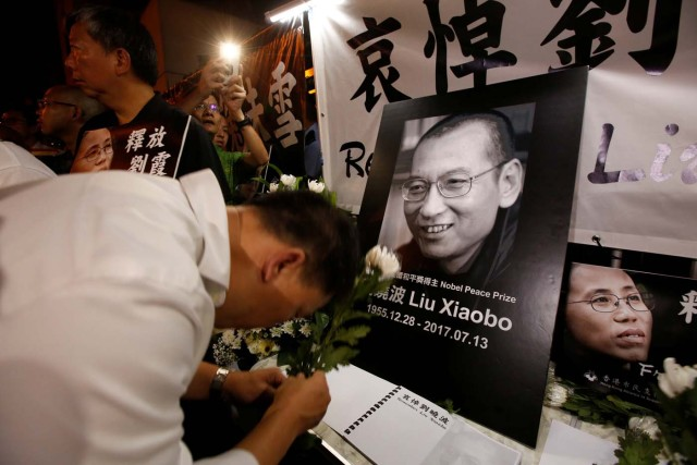 Pro-democracy activists mourn the death of Nobel Laureate Liu Xiaobo, outside China's Liaison Office in Hong Kong, China July 13, 2017. REUTERS/Bobby Yip