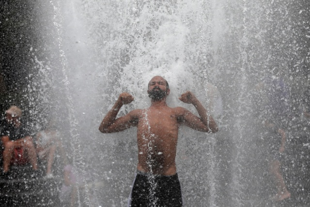 A man gets relief from hot weather as he cools off in a fountain in Washington Square Park in the Manhattan borough of New York City, U.S., July 13, 2017. REUTERS/Mike Segar
