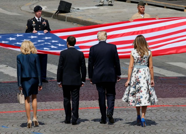 French President Emmanuel Macron, his wife Brigitte Macron, U.S. President Donald Trump and First Lady Melania Trump stand in front of the American flag at the end of the traditional Bastille Day military parade on the Champs-Elysees in Paris, France, July 14, 2017. REUTERS/Gonzalo Fuentes