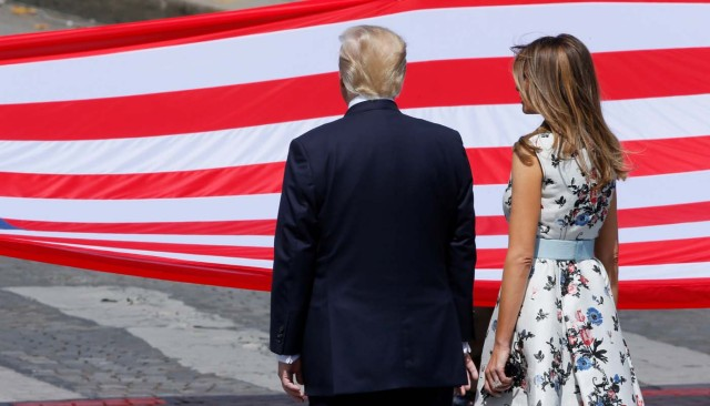 U.S. President Donald Trump and First Lady Melania Trump stand in front of the American flag at the end of the traditional Bastille Day military parade on the Champs-Elysees in Paris, France, July 14, 2017. REUTERS/Gonzalo Fuentes