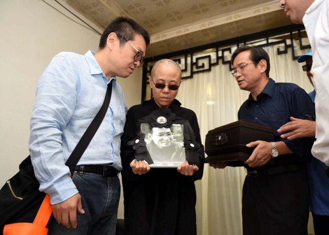 Liu Xia, wife of deceased Chinese Nobel Peace Prize-winning dissident Liu Xiaobo, holds his picture during his funeral in Shenyang, China in this photo released by Shenyang Municipal Information Office on July 15, 2017. Shenyang Municipal Information Office/via REUTERS. ATTENTION EDITORS - THIS IMAGE WAS PROVIDED BY A THIRD PARTY. NO RESALES. NO ARCHIVES. TPX IMAGES OF THE DAY