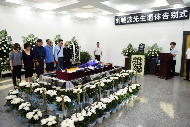 Liu Xia, wife of deceased Chinese Nobel Peace Prize-winning dissident Liu Xiaobo, and other relatives stand next to his coffin during his funeral in Shenyang, China in this photo released by Shenyang Municipal Information Office on July 15, 2017. Shenyang Municipal Information Office/via REUTERS. ATTENTION EDITORS - THIS IMAGE WAS PROVIDED BY A THIRD PARTY. NO RESALES. NO ARCHIVES.