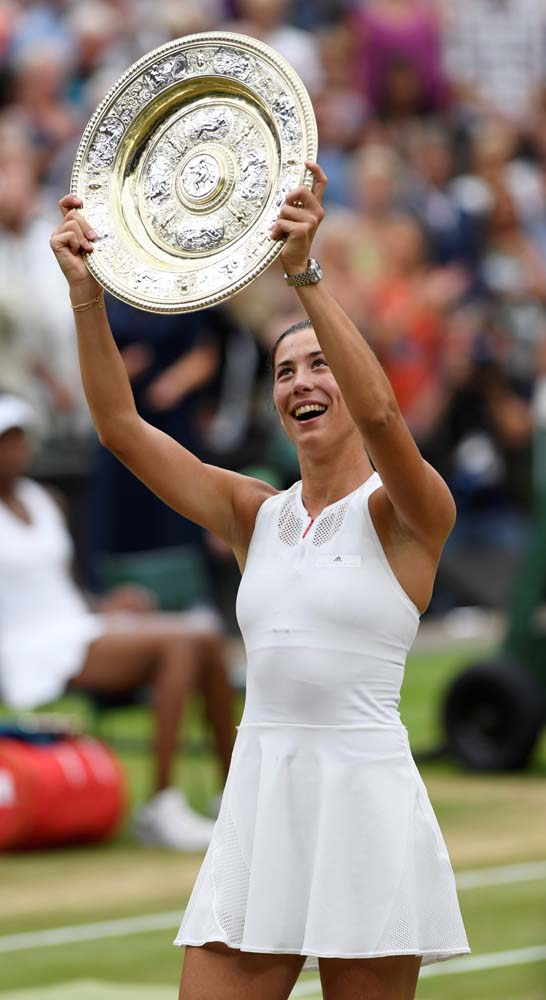 Tennis - Wimbledon - London, Britain - July 15, 2017 Spain's Garbine Muguruza holds the trophy as she celebrates winning the final against Venus Williams of the U.S. REUTERS/Tony O'Brien