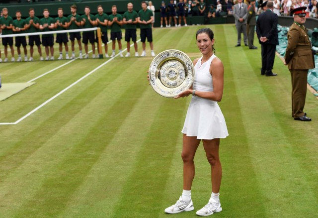 Tennis - Wimbledon - London, Britain - July 15, 2017 Spain's Garbine Muguruza poses with the trophy as she celebrates winning the final against Venus Williams of the U.S. REUTERS/Tony O'Brien
