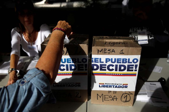 "A person votes during an unofficial plebiscite against Venezuela's President Nicolas Maduro's government and his plan to rewrite the constitution, in Caracas, Venezuela July 16, 2017. The writing on the boxes read ""The people decide, Liberator Movement."" REUTERS/Carlos Garcia Rawlins"