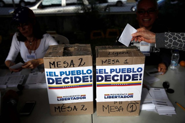 "A woman casts her vote during an unofficial plebiscite against Venezuela's President Nicolas Maduro's government and his plan to rewrite the constitution, in Caracas, Venezuela July 16, 2017. The writing on the boxes read ""The people decide, Liberator Movement."" REUTERS/Carlos Garcia Rawlins"