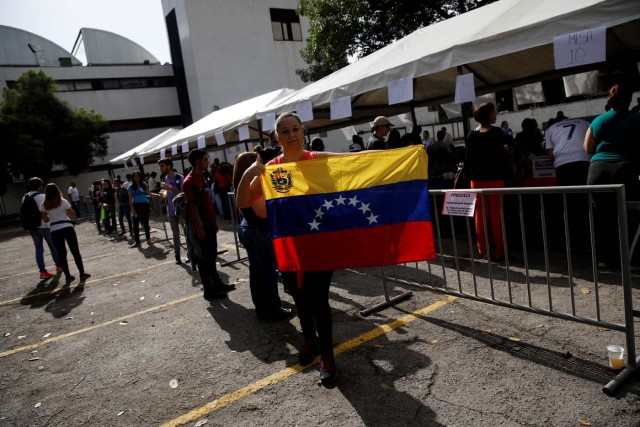 A woman holds a national flag at a polling station during an unofficial plebiscite against Venezuela's President Nicolas Maduro's government and his plan to rewrite the constitution, in Caracas, Venezuela July 16, 2017. REUTERS/Carlos Garcia Rawlins