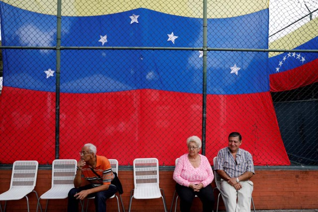 People sit in front of a national flag at a polling station during an unofficial plebiscite against Venezuela's President Nicolas Maduro's government and his plan to rewrite the constitution, in Caracas, Venezuela July 16, 2017. REUTERS/Andres Martinez Casares
