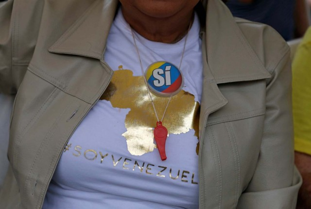 "A woman wears a pin in the national colours reading ""Yes"" at a polling station during an unofficial plebiscite against Venezuela's President Nicolas Maduro's government and his plan to rewrite the constitution, in Caracas, Venezuela July 16, 2017. The writing on the T-shirt reads: ""#I am Venezuela."" REUTERS/Andres Martinez Casares"