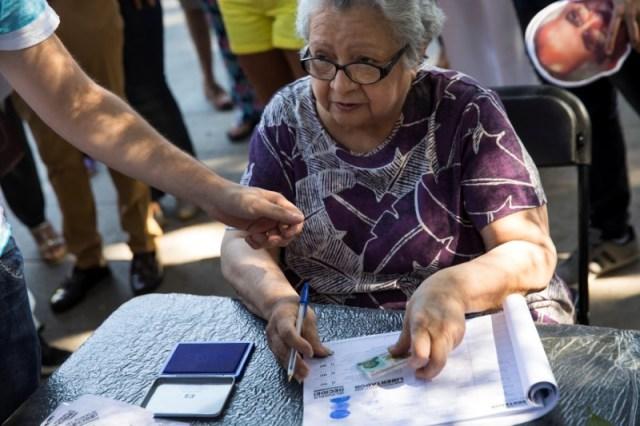 Una mujer se prepara para votar durante un plebiscito no oficial contra el presidente de Venezuela, Nicolás Maduro, en Madrid, España, el 16 de julio de 2017. REUTERS/Juan Medina
