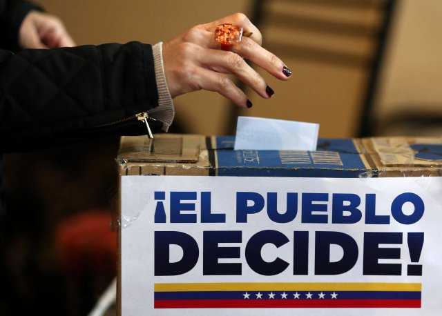 """A Venezuelan woman living in Argentina casts her vote during an unofficial plebiscite against President Nicolas Maduro's government in Buenos Aires, Argentina, July 16, 2017. The sign reads """"The people decide!"""". REUTERS/Marcos Brindicci"""