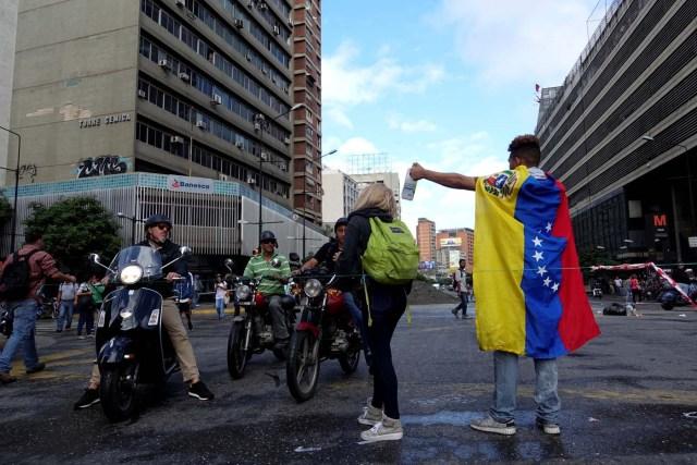 A demonstrator wearing a Venezuelan national flag blocks the street during a protest against Venezuelan President Nicolas Maduro's government in Caracas, Venezuela July 18, 2017. REUTERS/Carlos Garcia Rawlins