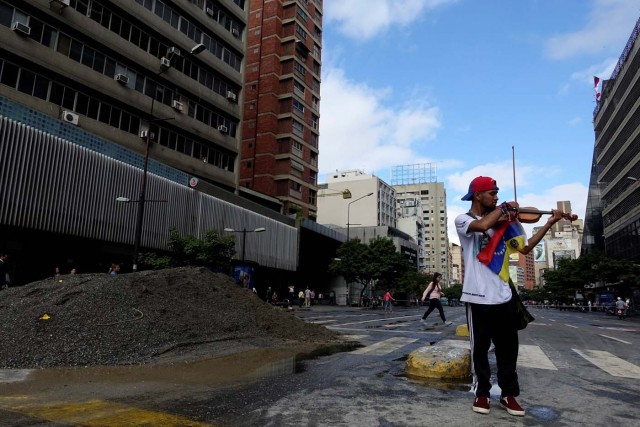 Venezuelan violinist Wuilly Arteaga plays the violin next to a pile of sand used by protesters to block the street during a protest against Venezuelan President Nicolas Maduro's government in Caracas, Venezuela July 18, 2017. REUTERS/Carlos Garcia Rawlins