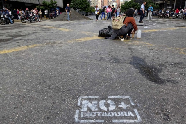 """People walk past a pile of sand used by protesters to block a street during a protest against Venezuelan President Nicolas Maduro's government in Caracas, Venezuela July 18, 2017. The graffiti reads """"No more dictatorship"""". REUTERS/Carlos Garcia Rawlins"""