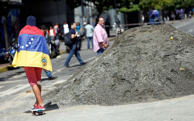 A man wearing the Venezuelan national flag over his shoulders rides a skateboard at an avenue blockade during a rally against Venezuelan President Nicolas Maduro's government in Caracas, Venezuela, July 18, 2017. REUTERS/Andres Martinez Casares