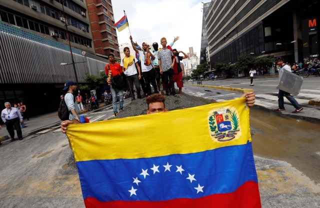 A demonstrator holds a Venezuelan national flag as others shout slogans at an avenue blockade during a rally against Venezuelan President Nicolas Maduro's government in Caracas, Venezuela, July 18, 2017. REUTERS/Andres Martinez Casares