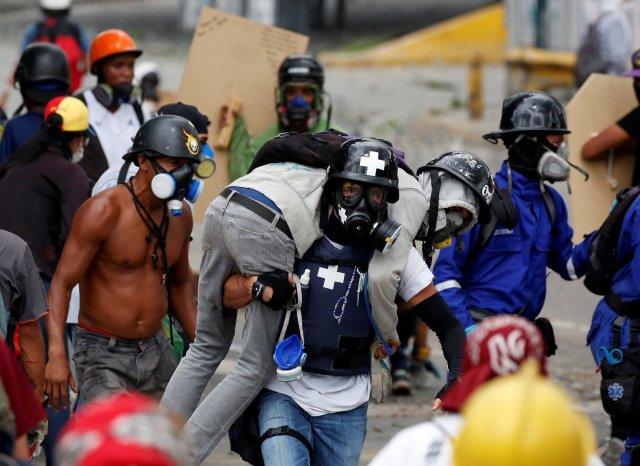 Uno de los heridos durante las manifestaciones de este sábado es rescatado por un integrante de grupos paramédicos. REUTERS/Carlos Garcia Rawlins