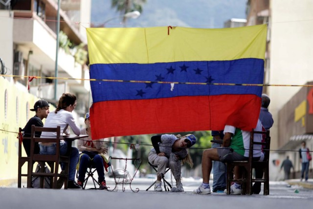 People are seen behind a barricade during a strike called to protest against Venezuelan President Nicolas Maduro's government in Caracas, Venezuela July 26, 2017. REUTERS/Ueslei Marcelino