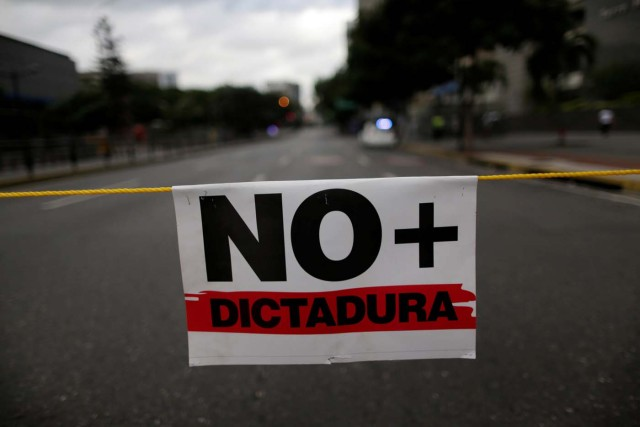 "A placard that reads ""No more dictatorship"" is seen during a strike called to protest against Venezuelan President Nicolas Maduro's government in Caracas, Venezuela July 26, 2017. REUTERS/Ueslei Marcelino"