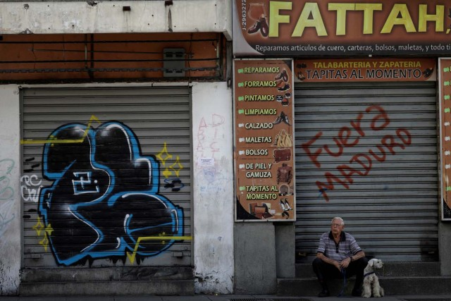 A man with a dog sits in front of a closed shop during a strike called to protest against Venezuelan President Nicolas Maduro's government in Caracas, Venezuela July 26, 2017. REUTERS/Ueslei Marcelino