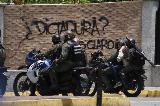 """Soldiers on motorcycles carry a person past a sign that says """"Dictatorship?"""" as the Constituent Assembly election was being carried out in Caracas, Venezuela, July 30, 2017. REUTERS/Carlos Garcia Rawlins"""
