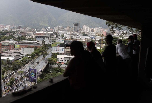 People watch from a balcony as opposition demonstrators set up a barricade on a bridge as clashes broke out with security forces while the Constituent Assembly election was being carried out in Caracas, Venezuela, July 30, 2017. REUTERS/Marco Bello