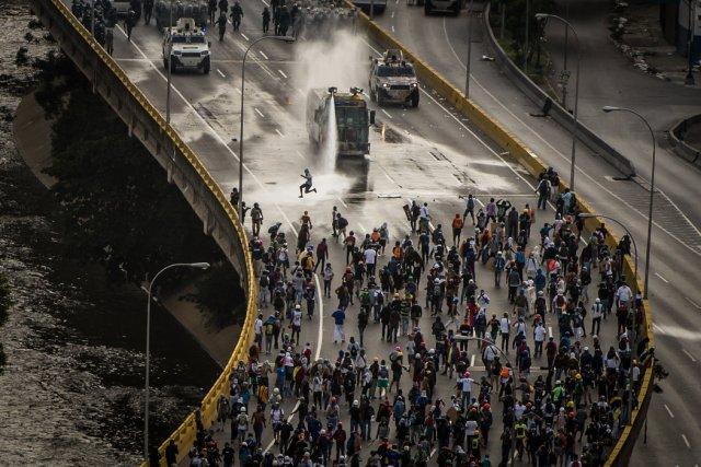 Una tanqueta usó su cañón de agua contra los manifestantes en la autopista Francisco Fajardo, en mayo. Credit Meridith Kohut para The New York Times