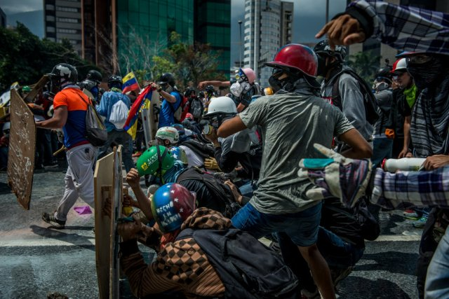 Manifestantes antigubernamentales lanzan piedras durante un enfrentamiento con fuerzas de seguridad en Caracas a principios de mayo. Credit Meridith Kohut para The New York Times