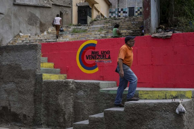 ACOMPAÑA CRÓNICA: VENEZUELA CRISIS - CAR001. CARACAS (VENEZUELA), 15/07/2017.- Un grupo de personas sube las escaleras de una barriada con las paredes decoradas con propaganda de la Asamblea Nacional Constituyente hoy, sábado 15 de julio de 2017, en Caracas (Venezuela). Con el éxito asegurado en las zonas privilegiadas de Caracas, donde el chavismo nunca tuvo predicamento, la consulta opositora sobre la Asamblea Constituyente que impulsa el presidente Nicolás Maduro se la juega ahora en los barrios populares que vieron en Hugo Chávez el mesías de la Revolución Bolivariana. EFE/Miguel Gutiérrez