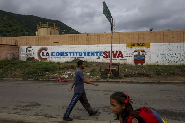 ACOMPAÑA CRÓNICA: VENEZUELA CRISIS - CAR002. CARACAS (VENEZUELA), 15/07/2017.- Un hombre y una niña caminan en frente de una pared decorada con propaganda de la Asamblea Nacional Constituyente en una barriada hoy, sábado 15 de julio de 2017, en Caracas (Venezuela). Con el éxito asegurado en las zonas privilegiadas de Caracas, donde el chavismo nunca tuvo predicamento, la consulta opositora sobre la Asamblea Constituyente que impulsa el presidente Nicolás Maduro se la juega ahora en los barrios populares que vieron en Hugo Chávez el mesías de la Revolución Bolivariana. EFE/Miguel Gutiérrez