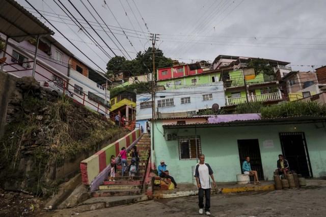 ACOMPAÑA CRÓNICA: VENEZUELA CRISIS - CAR003. CARACAS (VENEZUELA), 15/07/2017.- Un grupo de personas permanece en la calle de una barriada hoy, sábado 15 de julio de 2017, en Caracas (Venezuela). Con el éxito asegurado en las zonas privilegiadas de Caracas, donde el chavismo nunca tuvo predicamento, la consulta opositora sobre la Asamblea Constituyente que impulsa el presidente Nicolás Maduro se la juega ahora en los barrios populares que vieron en Hugo Chávez el mesías de la Revolución Bolivariana. EFE/Miguel Gutiérrez