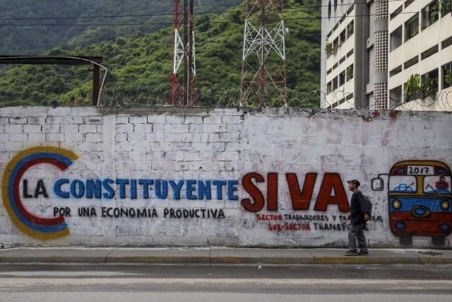ACOMPAÑA CRÓNICA: VENEZUELA CRISIS - CAR006. CARACAS (VENEZUELA), 15/07/2017.- Un hombre camina junto a una pared decorada con propaganda de la Asamblea Nacional Constituyente hoy, sábado 15 de julio de 2017, en Caracas (Venezuela). Con el éxito asegurado en las zonas privilegiadas de Caracas, donde el chavismo nunca tuvo predicamento, la consulta opositora sobre la Asamblea Constituyente que impulsa el presidente Nicolás Maduro se la juega ahora en los barrios populares que vieron en Hugo Chávez el mesías de la Revolución Bolivariana. EFE/Miguel Gutiérrez