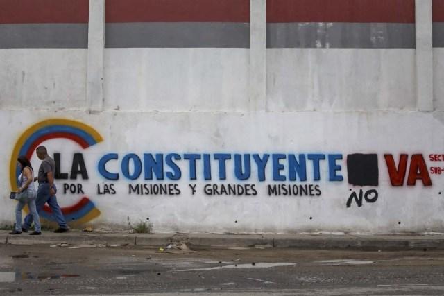 ACOMPAÑA CRÓNICA: VENEZUELA CRISIS - CAR007. CARACAS (VENEZUELA), 15/07/2017.- Un pareja camina frente a una pared con propaganda de la Asamblea Nacional Constituyente hoy, sábado 15 de julio de 2017, en Caracas (Venezuela). Con el éxito asegurado en las zonas privilegiadas de Caracas, donde el chavismo nunca tuvo predicamento, la consulta opositora sobre la Asamblea Constituyente que impulsa el presidente Nicolás Maduro se la juega ahora en los barrios populares que vieron en Hugo Chávez el mesías de la Revolución Bolivariana. EFE/Miguel Gutiérrez