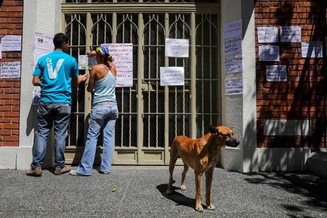 CAR04. CARACAS (VENEZUELA), 24/07/2017.- Una pareja pega carteles en rechazo a la Asamblea Constituyente hoy, lunes 24 de julio de 2017, en un colegio electoral de Caracas (Venezuela). Venezuela inicia hoy la semana decisiva para la elección de la Asamblea Nacional Constituyente convocada por el presidente, Nicolás Maduro, con los oficialistas entrando en la recta final de su campaña en medio de protestas y llamados a paro de los opositores en rechazo a esos comicios. EFE/Miguel Gutiérrez