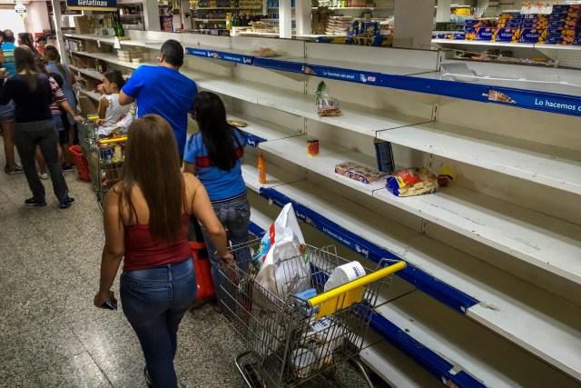 Personas buscan alimentos en un supermercado con estanterías parcialmente vacíos en Caracas (Venezuela). EFE/MIGUEL GUTIÉRREZ