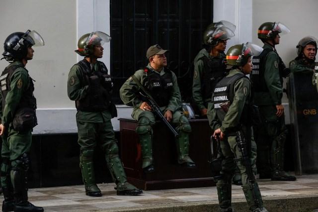 """Soldados de la Guardia Nacional Bolivariana (GNB) observan el asalto al Palacio Legislativo de la Asamblea Nacional de Venezuela el miércoles 5 de julio de 2017, en Caracas (Venezuela). Diputados del Parlamento venezolano, de mayoría opositora, lograron hoy salir de la sede del Legislativo tras más de siete horas de asedio por parte de grupos chavistas que irrumpieron de manera violenta dejando al menos ocho legisladores opositores lesionados y algunos daños materiales. El Parlamento denunció cerca de las 18.00 hora local (22.00 GMT) que 120 trabajadores, 108 periodistas y 94 diputados opositores estuvieron """"secuestrados por grupos armados afectos al Gobierno"""" y que habían llegado al lugar a las 08.00 hora local. EFE/Cristian Hernández"""