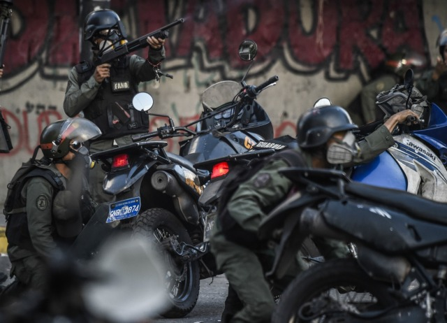 VENEZUELA-CRISIS-CONSTITUENT-ASSEMBLY-PROTEST Anti-government activists drag a police motorbike burnt after the explosion of an explosive device during a protest against the elections for a Constituent Assembly in Caracas on July 30, 2017. Deadly violence erupted around the controversial vote, with a candidate to the all-powerful body being elected shot dead and troops firing weapons to clear protesters in Caracas and elsewhere. Ronaldo SCHEMIDT / AFP