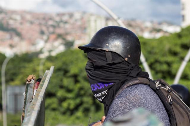 CAR301. CARACAS (VENEZUELA), 30/07/2017.- Manifestantes opositores bloquean una calle en rechazo a las elecciones de la Asamblea Nacional Constituyente hoy, domingo 30 de julio de 2017, en Caracas (Venezuela). Venezuela amaneció hoy en tensa calma y con focos de violencia y de enfrentamientos entre manifestantes antichavistas y las fuerzas de seguridad desde muy temprano, en esta jornada en la que se celebran las elecciones de la Asamblea Nacional Constituyente impulsada por el Gobierno de Nicolás Maduro. EFE/Nathalie Sayago