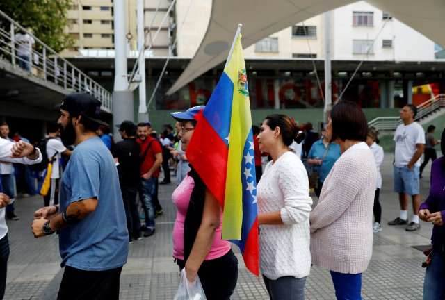 A woman holds a national flag as she stands in line along with others to cast her vote during an unofficial plebiscite against Venezuela's President Nicolas Maduro's government and his plan to rewrite the constitution, in Caracas, Venezuela July 16, 2017. REUTERS/Andres Martinez Casares