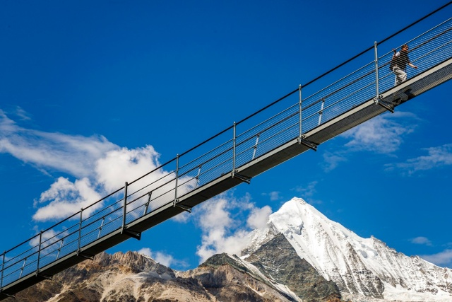 "A person walks on the ""Europabruecke"",  supposed to be the world's longest pedestrian suspension bridge with a length of 494m, after the official inauguration of the construction in Randa, Switzerland, on Saturday, July 29, 2017. The bridge is situated on the Europaweg that connects the villages of Zermatt and Graechen. (Valentin Flauraud/Keystone via AP)"