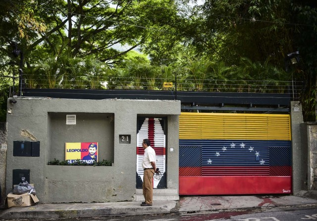 A journalist stands outside the house of Venezuelan opposition leader Leopoldo Lopez in Caracas on August 1, 2017 just hours after he was taken away from his home by the intelligence service. The Venezuelan intelligence service arrested opposition leaders Leopoldo Lopez and Antonio Ledezma overnight Monday, relatives said, a day after a vote to choose a much-condemned assembly that supersedes parliament. Lopez and Ledezma were both already under house arrest when they were picked up by the intelligence service known by its in acronym Sebin, the wife of Lopez and children of Ledezma said separately. / AFP PHOTO / Ronaldo SCHEMIDT